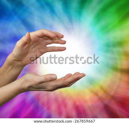 Color healing therapist sensing color energies - Female hands cupped in energy sensing position with a rainbow vortex behind and a ball of white energy in the center