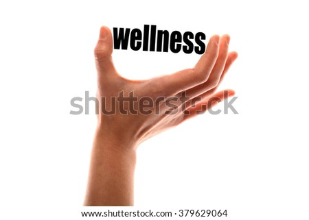 "Color horizontal shot of a of a hand squeezing the word ""wellness""."