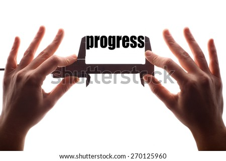"Color horizontal shot of two hands holding a caliper and measuring the word ""progress"". - stock photo"