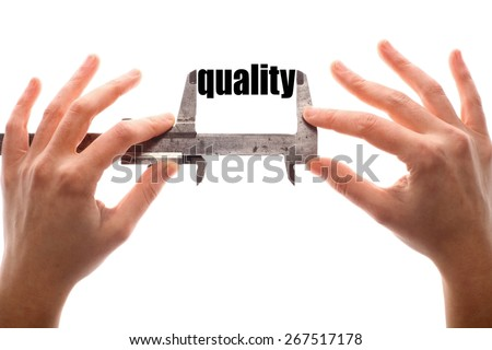 """Color horizontal shot of two hands holding a caliper and measuring the word """"quality"""". - stock photo"""
