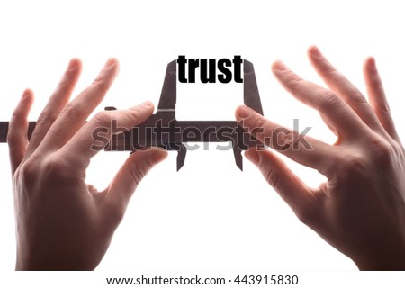 "Color horizontal shot of two hands holding a caliper and measuring the word ""trust""."