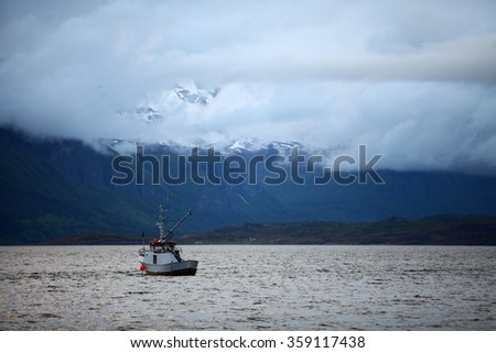 Color image of a boat on a lake and some snowy mountains.