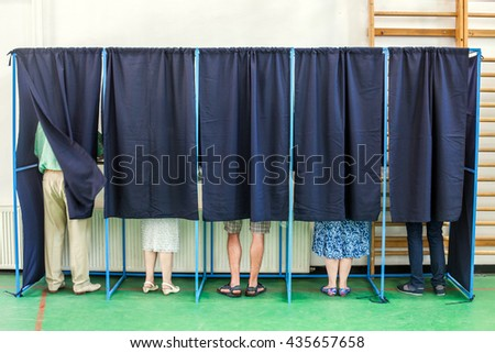 Color image of some people voting in some polling booths at a voting station. - stock photo