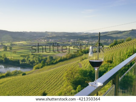 color landscape stock photo of glass of red wine on balcony overlooking Piedmont wine country vineyards with a lake and willow trees in foreground and vineyards in background