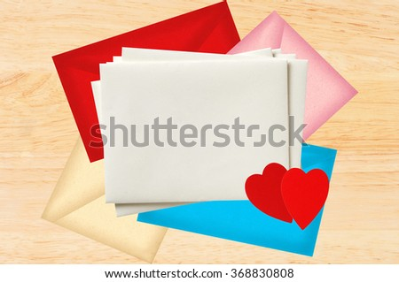 Color letters envelopes with red hearts over wooden texture