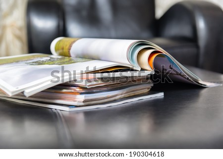Color magazines in leather living room - stock photo