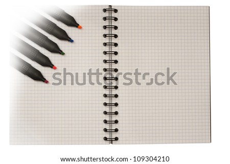 Color markers on opened notebook with a metal spiral and white sheets in a cell isolated with clipping path on white background