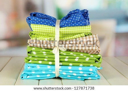 Color mottled fabrics on wooden table on room background - stock photo