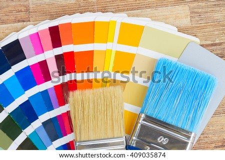 Color palette guide and brushes close up on wooden background - stock photo