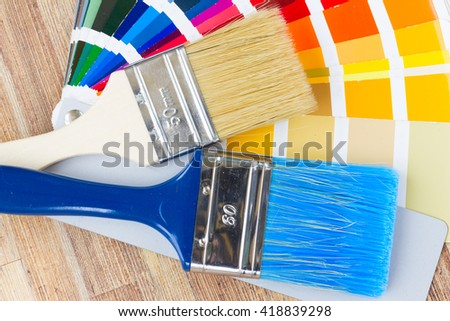 Color palette guide and brushes close up on wooden table - stock photo