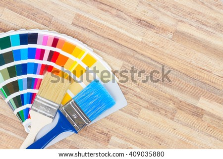 Color palette guide and brushes on wooden background - stock photo