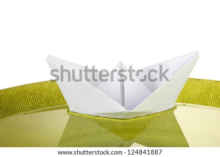Color paper ship in water on green plate, close-up
