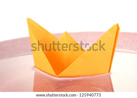 Color paper ship in water on pink plate, close-up