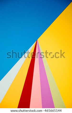 Color papers geometry flat composition background with yellow orange red violet and blue tones.