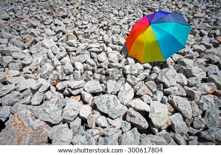 Color pattern of an umbrella with stone as background. - stock photo