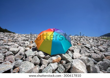 Color pattern of an umbrella with the sky and stone as background. - stock photo