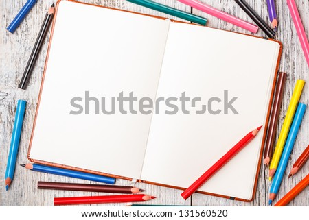 Color pencil and notepad on rustic wooden table - stock photo