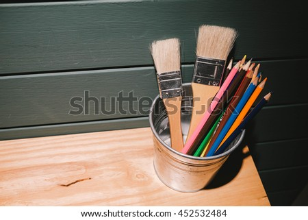 color pencil andpainting brush on wooden top and dark blue space with the light from lamp