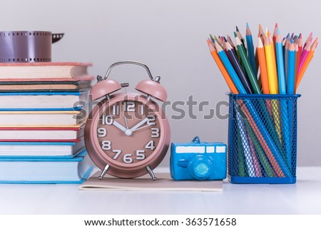 color pencil box , alarm clock and stack of book on wooden table - stock photo