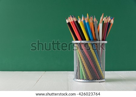 color pencil box on wooden table - stock photo
