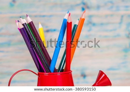 color pencil in red watering can. - stock photo