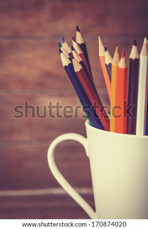 Color pencil in the cup on wooden background - stock photo