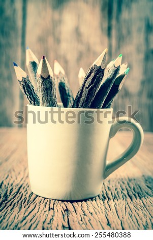 color pencil made of branches in coffee cup  ; vintage filtered style - stock photo