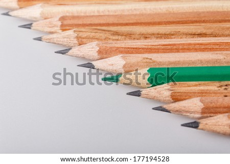 Color pencil stands out against a series of graphite pencils - stock photo