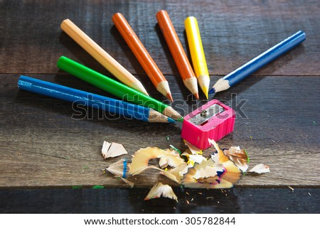 COLOR PENCILS AND PENCIL SHARPENER ON THE VINTAGE WOODEN TABLE TEXTURE BACKGROUND (SELECTIVE POINT FOCUS) - stock photo