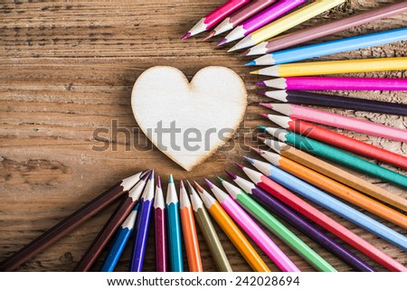 Color pencils around wood texture heart shape on background Empty space idea of concentration attraction to nucleus center circle radius unity concept of leadership community, team focused on one goal - stock photo