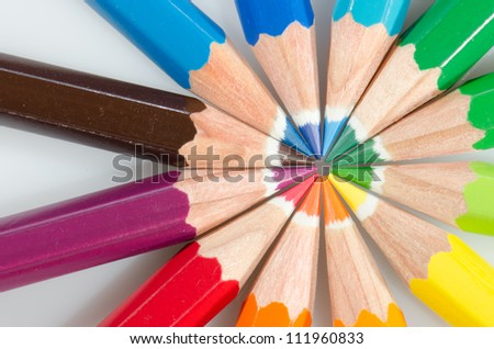 Color pencils arranged in roygbiv on white background