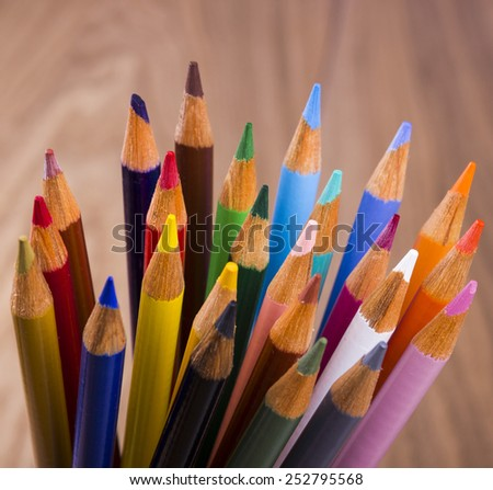 Color pencils in arrange in color wheel colors on wood background - stock photo