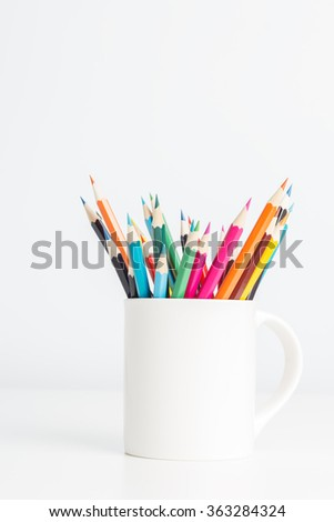 Color pencils in cup on white table background