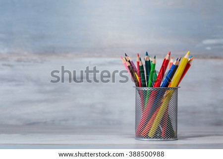 color pencils in the stand holder on the wood vintage background