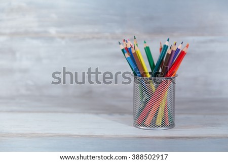 color pencils in the stand holder on the wood vintage background copy space