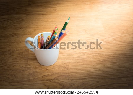 Color pencils in white coffee cup on wooden background - stock photo