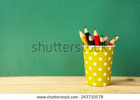 color pencils in yellow polka dot paper glass over retro green background  - stock photo