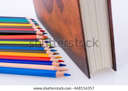 color pencils of various colors near the Holy Quran on a white background
