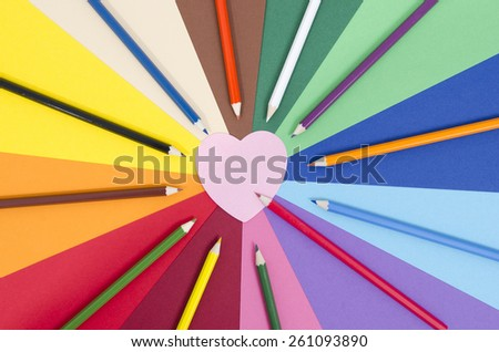Color pencils on paper with pink heart memo note. All colors pencils arranged in a circle on rainbow color paper with blank post it note. - stock photo