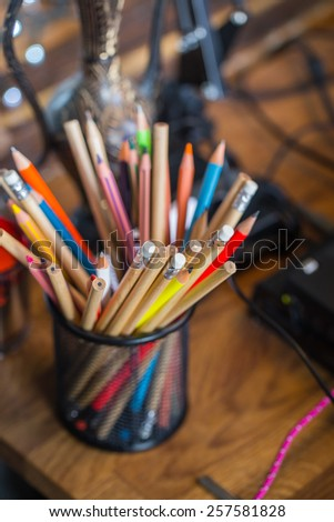 Color pencils on the table with background lights
