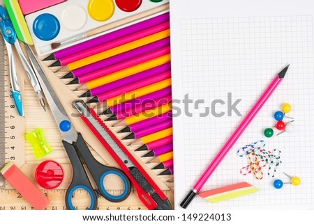 Color pencils with bright writing-materials over wooden surface