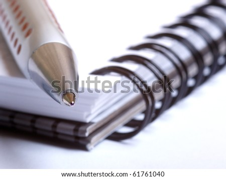Color photo of a ballpoint pen and notebook
