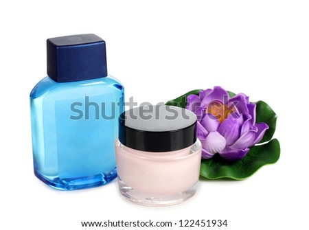Color photo of a glass bottle with cream and flower