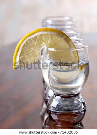 Color photo of a glass cup with tequila and lemon - stock photo