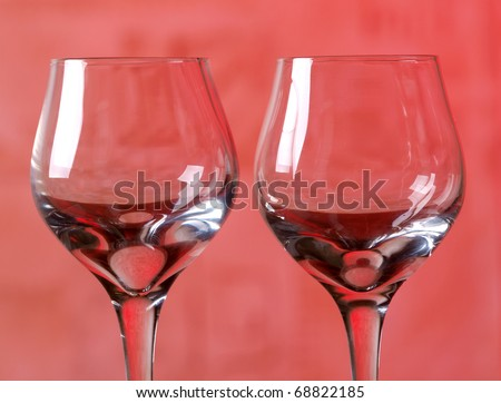 Color photo of a glass of wine glasses in red background