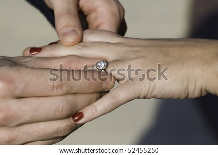 Color photo of a man putting an engagement ring on a female's hand.