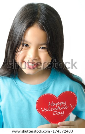 Color photo of a 7 year old, asian black haired girl  holding an heart-shaped  - stock photo