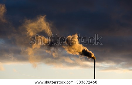 Color photograph of industrial buildings at sunset. smokestacks contributing  to the pollution in the air. dense smoke background. Smoke raising from a chimney. Tube and smoke - stock photo