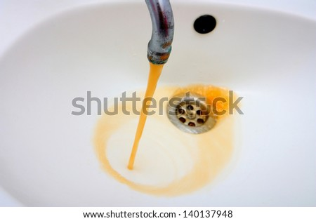 Color photography of a rusty water what run from a faucet - stock photo