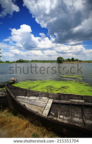 Color picture of a wooden boat on a river bank.
